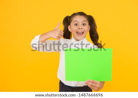 This is genius. Happy girl genius holding blank paper sheet on yellow background. Genius child giving thumbs up gesture for empty poster. Liking her genius idea, copy space.