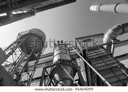 This is industrial object with flue gas stack. There are many metallic constructions on the photo.