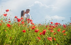 This is love. family summer vacation. happy man and woman in love enjoy spring weather. happy relations. girl and guy in field. bride and groom. romantic couple with red poppy flowers