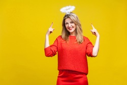 This is me angel! Portrait of proud adorable young woman with bright makeup in red casual clothes standing, pointing at hola on her head and smiling. indoor studio shot isolated on yellow background