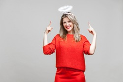 This is me angel! Portrait of proud adorable young woman with bright makeup in red casual clothes standing, pointing at hola on her head and smiling. indoor studio shot isolated on gray background