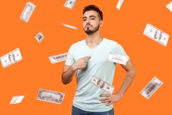 This is me, dollar millionaire! Portrait of arrogant self-confident man pointing at chest, looking proud and egoistic. money falling and he is rich. indoor studio shot isolated on orange background