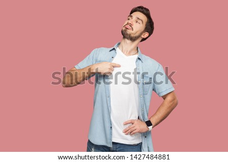 This is me. Portrait of proud haughty handsome bearded young man in blue casual style shirt standing, looking away and pointing himself. indoor studio shot, isolated on pink background.