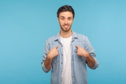 This is me! Portrait of self-confident narcissistic man in worker denim shirt smiling satisfied and pointing himself, feeling self-important, proud, famous. studio shot isolated on blue background