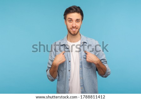 This is me! Portrait of self-confident narcissistic man in worker denim shirt smiling satisfied and pointing himself, feeling self-important, proud, famous. studio shot isolated on blue background Foto stock ©