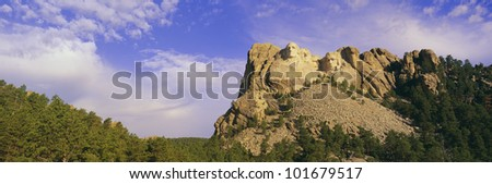 This is Mount Rushmore National Monument set into the mountain showing its natural surroundings against a blue sky.