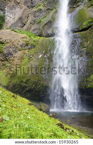 This is Multnomah WaterFall Upper Pool Plunging mist into pool over green hill after a 542 foot drop