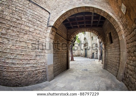 This is one of the entrances to Sant Felip Neri square, a calm, small place located (almost hidden) at the gothic quarter of Barcelona. We can also see part of the facade of Sant Felip Neri's church.