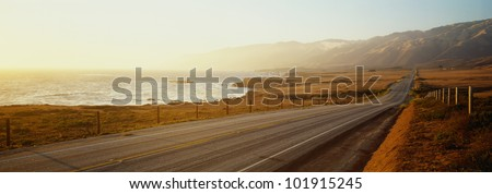 This is Route 1, also known as the Pacific Coast Highway. The road is situated next to the ocean with the mountains in the distance.