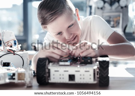This is so interesting. Selective focus on a focused preteen boy focusing his attention on a robotic machine while enjoying the process of working on a school technological process. #1056494156