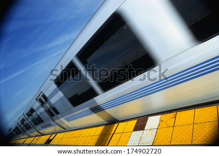 This is the Bart Metro Rail. It is the Bay area rapid transit system. The train is shown at an angle with the end of the train getting smaller into infinity next to a tile floor platform.
