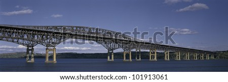 This is the Beacon Bridge which is over the Hudson River. It is a large steel bridge. The water and sky are blue.
