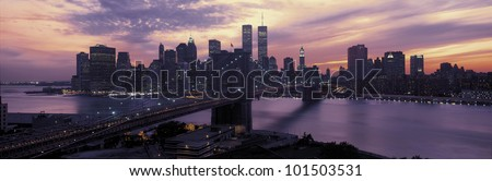 This is the Brooklyn Bridge over the East River and the Manhattan skyline at sunset. There is a purple cast to the sky and the lights to the buildings are starting to come on.