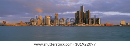 This is the Detroit skyline at sunrise. It shows the Detroit River in the foreground.