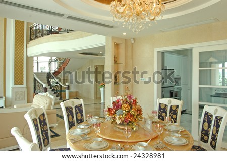 this is the dining room,  a few dining chair around a table,there is a bottle of flowers on the table.