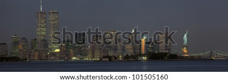 This is the downtown Manhattan skyline and Statue of Liberty. It is the view at dusk. The World Trade towers dominate the left hand side, the Statue of Liberty is on the right. - stock photo