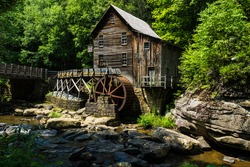 This is the Glade Creek Grist Mill located in Babcock State Park in West Virginia. This area is heavily forested with the Glade Creek running under the  bridge past the mill.