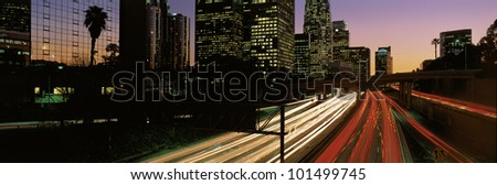 This is the Harbor Freeway with rush hour traffic at sunset. The yellow and red streaked lights from the cars are on the freeway.
