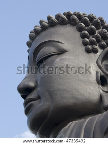 This is the head of a large buddha against a blue sky backdrop.