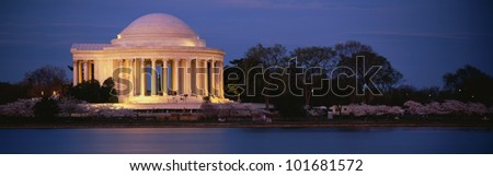 This is the Jefferson Memorial next to the Tidal Basin. Cherry blossoms are blooming on the trees surrounding it at dusk.