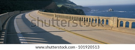 This is the Pacific Coast Highway on the Bixby Bridge. It is next to the mountainous coast and the Pacific Ocean.