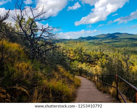 This is the path that leads to the top of Thumb Butte Trail in Prescott National Forest in Prescott, AZ. The railings are there due to a steep drop off. A view of the surrounding area can be seen.