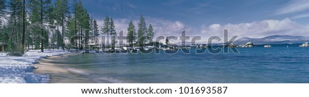 This is the sandy beach at Lake Tahoe. It shows the turquoise water in the winter after a snow storm.