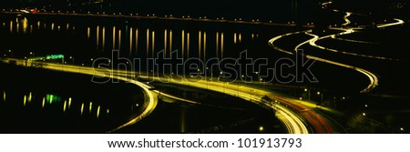 This is the Theodore Roosevelt Bridge over the Potomac River at night. There are streaked lights from the cars on the freeway and reflections from the lights on the road in the river.