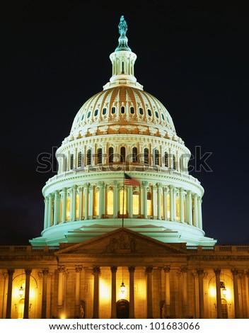 This is the U.S. Capitol at dusk. The lights are on in the rotunda. We see it against a clear night sky.