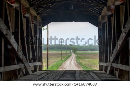 this is the view from inside a covered bridge, of the long dirt road on the other side, and the vintage structure within