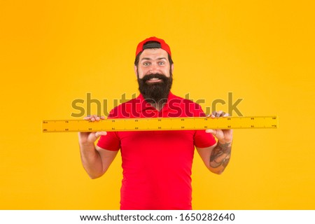 this is too big. Measuring a line. back to school. Teacher hold metric ruler yellow wall. bearded man preparing for maths and geometry lesson. brutal service worker with ruler. measure the length.