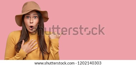 Photo of This knocks me from feet. Excited brunette young woman has bated breath, points with thumb, wears beige hat and yellow sweater, isolated over pink background with free space for your promotion