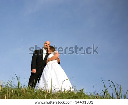 This lovely bride and groom are embracing and dreaming of their new life together.  Grass in the foreground and blue sky in the background.