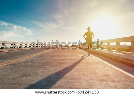 This man is jogging on street among the sun shines down light. #691249138