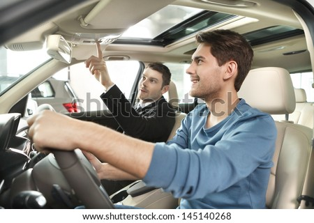 This model comes with added features Handsome young salesman showing all the car features to the customer