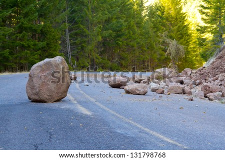This national forest road is blocked by a land slide of rock and debris to where it is a hazard for drivers in cars