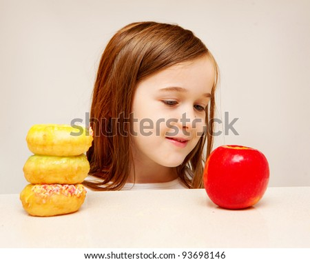 This photo depicts a young girl making decisions between healthy food and unhealthy food.