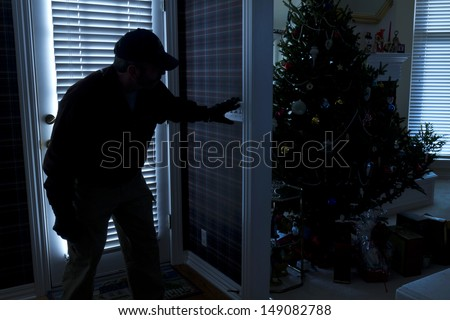 This photo illustrates a burglary or thief breaking into a home at night through a back door during the Christmas Holiday Season View from inside the residence