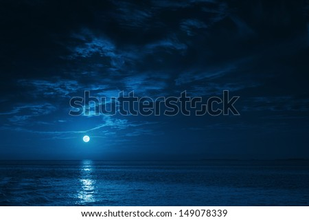 This photo illustration of a deep blue moonlit ocean at night with calm waves would make a great travel background for any coastal region or vacation. #149078339