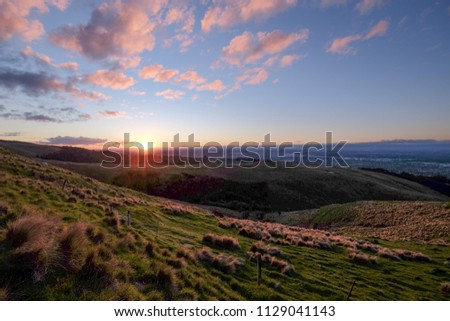 This photo is taken during road trip in New Zealand. It was approaching sunset and we drove to the top of the mountain. The view is excellent. The sky is very colorful and vibrant. This is perfect.