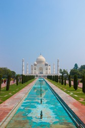 This photo is taken in Agra, India. It shows Taj mahal which is one of the seven wonders of the world and unesco world heritage sites. You can see the garden and the taj in this photo
