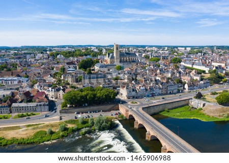 This photo was taken in France, Burgundy, Nevers in summer. We can see the Loire in the foreground, the Loire bridge in stone and the city of Nevers dominated by its cathedral in the background. Zdjęcia stock ©
