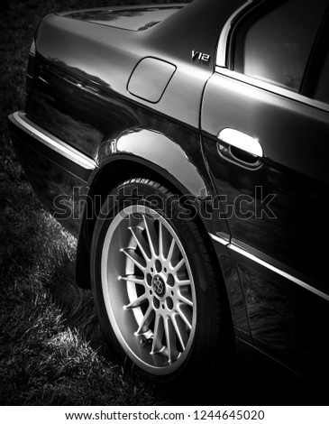 This photo was taken in Kettering, Northamptonshire / United Kingdom - May 6, 2018: The rear wheel of a retro BMW 7 Series luxury car. #1244645020