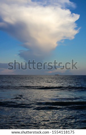 This photos shows some fluffy clouds over the ocean during a sunset. #1554118175