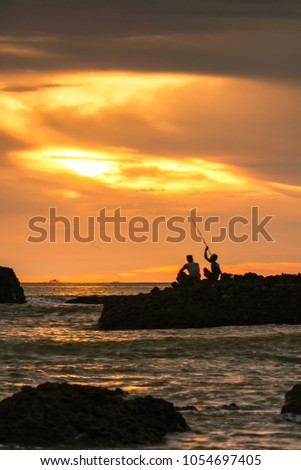 this pic is taken at Ciletuh, West Java, Indonesia, Asia. there is two man fishing at sunset. they work together with one rod to fishing in the top of rock.
