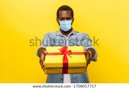 This present for you! Portrait of happy man with surgical medical mask giving wrapped gift box and smiling at camera. or delivery on quarantine time. indoor studio shot isolated on yellow background