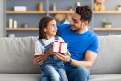This Present Is For You. Portrait of loving girl sitting on dad's lap and greeting him with father's day or birthday, holding wrapped gift box, happy family celebrating holiday together at home