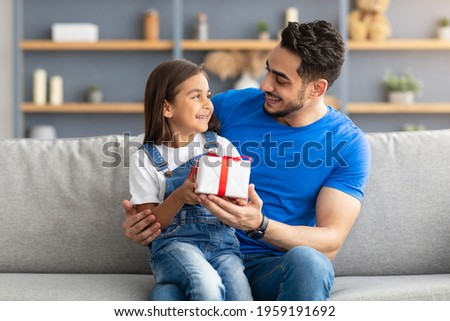 This Present Is For You. Portrait of loving girl sitting on dad's lap and greeting him with father's day or birthday, holding wrapped gift box, happy family celebrating holiday together at home Stockfoto ©