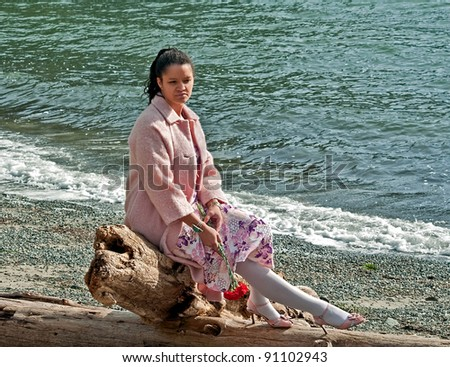 This pretty multi ethnic woman conveys many emotions, sadness, dejected, lonely as she\'s sitting on driftwood at a beach, with some red carnation flowers hanging down, as if she as lost love.