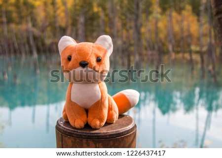 This red fox stuffed toy is sitting on the fence with background of Blue Pond that located at Biei Town, Hokkaido- Japan. This photo was taken during autumn season on the middle of October 2018.